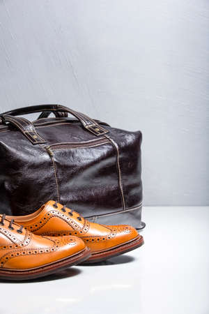 Male Tanned Full Broggued Oxford Calf Leather Shoes Along With Dakr Brown Leather Travel Bag on White Surface.Vertical Image