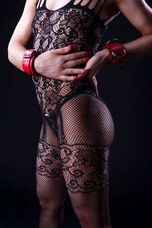 Alluring Caucasian Female in Sexy Mesh Body Suit Prepared for Sado-Masochism Play. Over Black Background. Vertical  Image