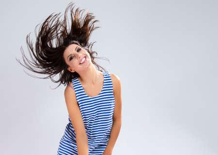 Portrait of Caucasian Brunette Girl in Sweatshirt.Posing Against White.Making Hair Flying.Horizontal Image