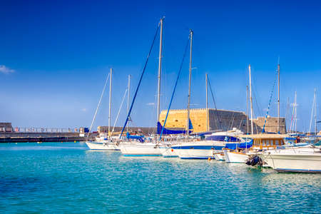 Koules Fortress and Old Venetian Harbour with Lines of Sailing Fishing Boats At Noon in Heraklion City, Greece. Horizontal Image