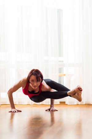 Yoga Concepts. Caucasian Woman Practicing Yoga Exercise Indoors At Bright Afternoon. Sitting in Ashtavakrasana Pose During Solitude Meditation Session.Vertical Image
