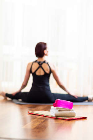 Backview of Tranquil Caucasian Woman in Yoga Pose Indoors. Posing With Stretched Legs in Front of Big Window With Stack of  White Towels with Water Bottle in  Foreground.Vertical image