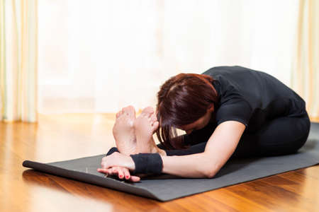 Yoga Concept. Caucasian Woman Practicing Yoga Exercise Indoors At Bright Afternoon. Sitting in Pashchimottasana Pose During Solitude Meditation Session. Equipped In Black Top Bra and Black Pants.Horizontal Image