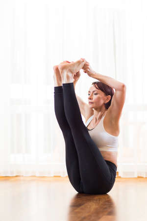 Caucasian Bunette Woman Practicing Yoga and Pilates, Doing Paripurna Navasana Exercise on Floor Mat. Sitting Indoors In Front of Big Sunny Window. in Studio.Vertical Image Banque d'images