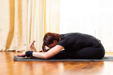 Yoga Concept. Caucasian Woman Practicing Yoga Exercise Indoors At Bright Afternoon. Sitting in Pashchimottasana Pose During Solitude Meditation Session. Equipped In Black Top Bra and Black Leggings.Ho