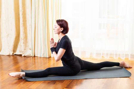 Caucasian Woman Practicing Yoga Exercise Indoors At Bright Afternoon. Sitting in Hanu Manasana Pose During Solitude Meditation Session. Wearing Black Top Shirt  and Black Leggings.Horizontal Image