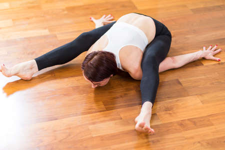 Caucasian Sporty Woman Doing Yoga Practicing indoors. Sitting in Back and Legs Separated Split Stretching Posture.Horizontal Image
