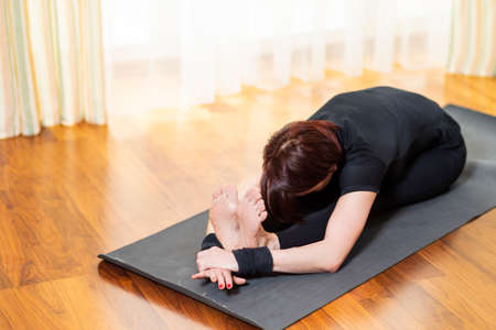Caucasian Woman Practicing Yoga Exercise Indoors At Bright Afternoon. Sitting in Pashchimottasana Pose During Solitude Meditation Session. Equipped In Black Top Bra and Black Leggings.Horizontal Orientation