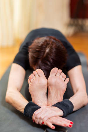 Yoga Concept. Caucasian Woman Practicing Yoga Exercise Indoors At Bright Afternoon. Sitting in Pashchimottasana Pose During Solitude Meditation Session. Equipped In Black Top Bra and Black Leggings.Vertical Shot