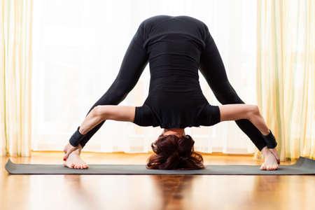 Caucasian Woman Practicing Yoga Exercise Indoors At Bright Afternoon. Sitting in Prasarita Padottanasana Pose During Solitude Meditation Session. Wearing Black Top Shirt  and Black Leggings.Horizontal Shot 写真素材 - 114742553