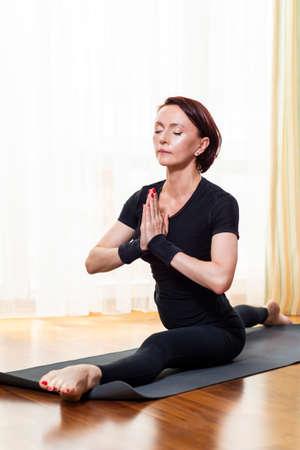 Caucasian Woman Practicing Yoga Exercise Indoors At Bright Afternoon. Sitting in Hanu Manasana Pose During Solitude Meditation Session. Wearing Black Top Shirt  and Black Leggings.Vertical Shot