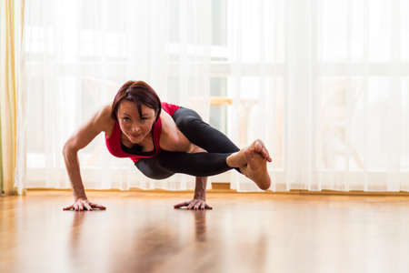 Yoga Concepts. Caucasian Woman Practicing Yoga Exercise Indoors At Bright Afternoon. Sitting in Ashtavakrasana Pose During Solitude Meditation Session.Horizontal Image