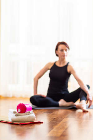 Caucasian Yoga Woman Blurred on Background. Sport Accessories in Foreground In Focus.Vertical Orientation 写真素材 - 114742835