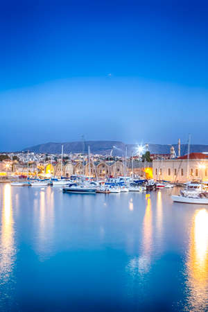 Travel Concepts. Picturesque Image of Old Venetian Harbour of Chania with line of Fisihing Boats and Yachts in the Foregound At Blue Hour in Crete. Vertical Image Composition Фото со стока - 115813245