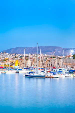 Travel Concepts. Picturesque Image of Old Venetian Harbour of Chania with line of Fisihing Boats and Yachts in the Foregound At Blue Hour in Crete. Vertical Composition 版權商用圖片