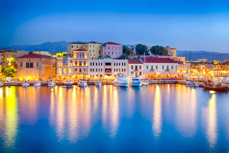 Travel Concepts. Picturesque Image of Old Venetian Harbour of Chania with Fisihing Boats and Yachts on the Foregound Taken At Blue Hour in Crete, Greece.Horizontal Orientation Фото со стока - 115813476