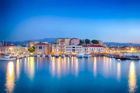 Travel Concepts. Picturesque Image of Old Venetian Harbour of Chania with Fisihing Boats and Yachts on the Foregound Taken At Blue Hour in Crete, Greece.Horizontal image Фото со стока - 115813509