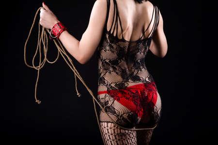 Mujer en lencería sexy BDSM posando con accesorios de cuerda para juego BDSM. Con esposas rojas y pantimedias de red. Orientación horizontal de la imagen