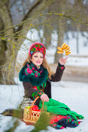 Winter Fashion Concepts. Caucasian Girl in Green Dress and Flowery Pattern Kokoshnik with Accessories. Posing With Samovar And Bread Rings in Winter Forest. Vertical Image
