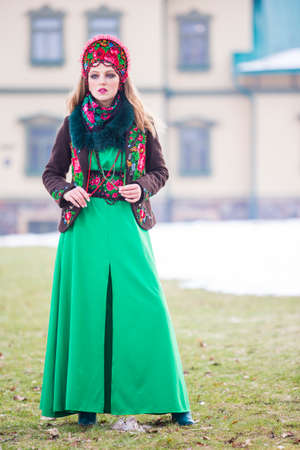 Winter Unique Female Fashion Concepts. Caucasian Blond Girl in Stylish Green Dress and Kokoshnik. Posing in Winter Outdoors.Vertical Image