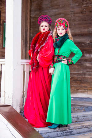 Two Young Ladies in Fashionable Unique Dresses With Kokoshnik Posing Against Old Wooden House in Winter Outdoors. Vertical Image Orienation