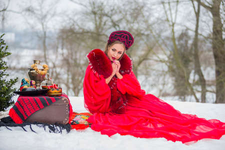 Winter Fashion Concepts. Caucasian Girl in Red Unique Dress and Kokoshnik with Accessories. Posing With Samovar and Retro Suitcase in Winter Forest. Horizontal Image