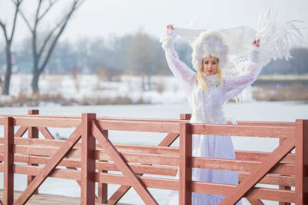 Woman Winter Fashion. Portrait of Sensual Caucasian Blond in Knitted White Dress and Kerchief with Fur Kokoshnik.Posing on Bridge in Winter.Horizontal Image Composition