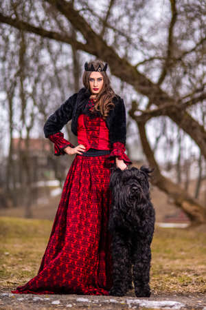 Beautiful Princess in Red Dress And Black Fur Jacket Posing in Crown Along with Her Dog in Forest During Early Spring. Art Photography.Vertical image