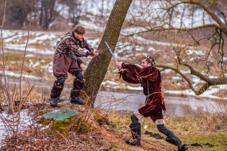 Art Photography. Two Knights Fighting on Swords in Forest Outdoors Against River On Background.Horizontal Shot