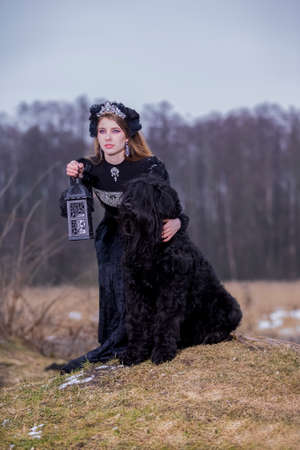 Costume Play. young Caucasian Female in Medieval Black Dress Posing With Lamp and Dog Over Hill. Vertical Image Orientation