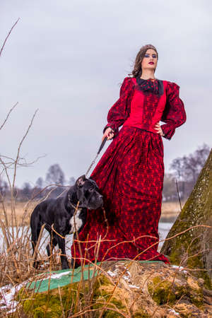 Art Photography Concepts. Beautiful Fairy Princess in Red Dress with Crown and Her Dog on Leash in Forest on Hill During Early Spring. Vertical Shot