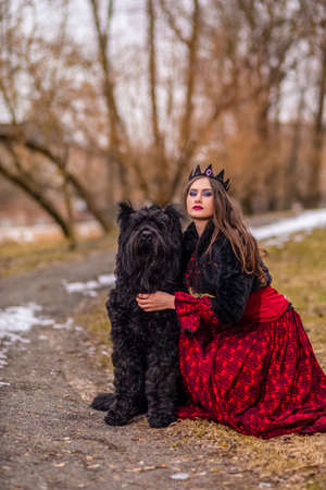 Beautiful Princess in Red Dress And Black Fur Jacket Posing in Crown Along with Her Dog in Forest During Early Spring. Art Photography.Vertical Shot