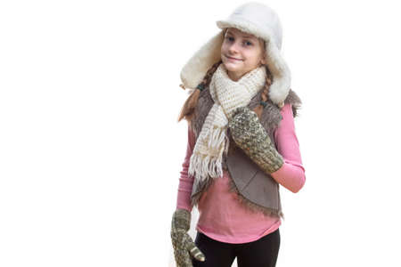 Winter Kids Fashion And Holidays Ideas. Smiling Caucasian Girl In Pink Vest and White Winter Hat, Scarf and Mittens. Over Pure White. Horizontal image Stock fotó