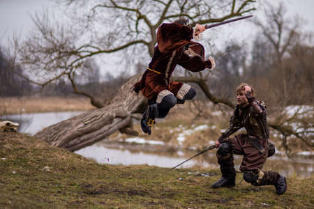 Art Photography. Two Knights Fighting on Swords in Forest Outdoors Against River On Background.Horizontal Image