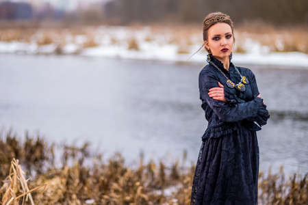 Passionate Caucasian Brunette Female in Art Dress with Necklace and Crown Posing Against River Outdoors. Horizontal Shot