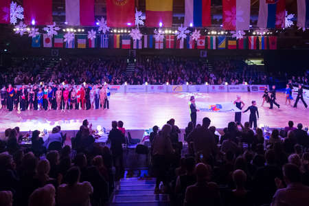 Riga, Latvia-December 15, 2018: Professional Adult Dance Couples Posing Together on Dancefloor With WDSF Flag Demonstration on WDSF Baltic Grand Prix-2108 Championship in December 15, 2018 in Riga, Latvia. Banque d'images - 119317209