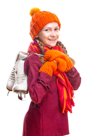 Portrait of Positive Laughing Caucasian Girl in Winter Clothes Posing with Ice Skates In Both Hands Against Pure White Background.Vertical Image Composition