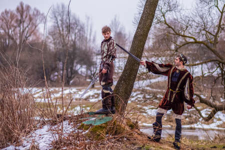 Costume Play Art Photography. Two Knights Fighting on Swords in Forest Outdoors Against River On Background.Horizontal Image Imagens