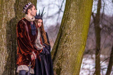 Art Photography and Cosplay.Caucasian Couple as King and Queen in Fur Medieval Outfit With Crowns Posing Together Outdoor.Horizontal Image Composition