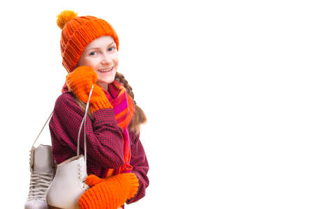 Portrait of Positive Laughing Caucasian Girl in Winter Clothes Posing with Ice Skates In Both Hands Against Pure White Background.Horizontal Orientation