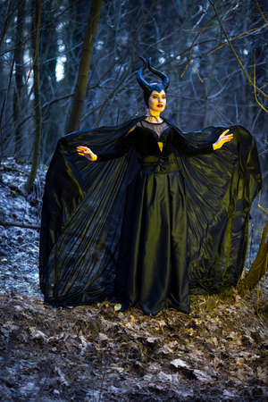 Costume Drama Play. Mysterious and Magical Woman with Horns Posing in Spring Empty Forest with Wavy Shawl. Horizontal Orientation