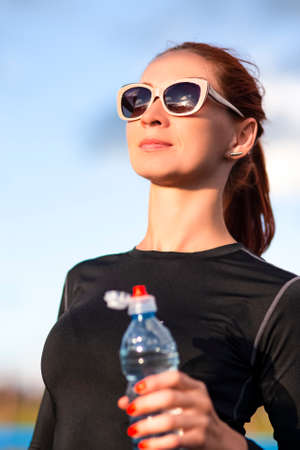 Fitness Caucasian Woman in Sportwear and Sunglasses With Water from Bottle Outdoors.Vertical image