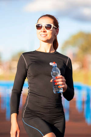 Portrait of Smiling Caucasian Woman in Sportwear and Sunglasses With Water from Bottle Outdoors.Vertical Image Composition