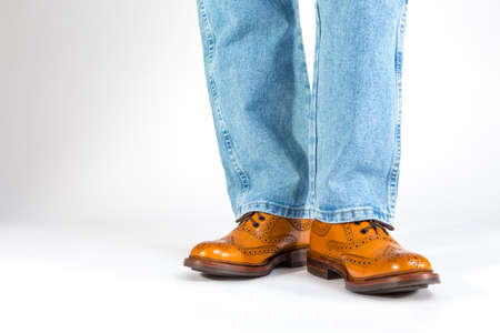 Footwear Concept. Closeup Front View of Mens Legs in Brown Oxford Brogue Shoes. Posing in Blue Jeans Against White. Horizontal Image