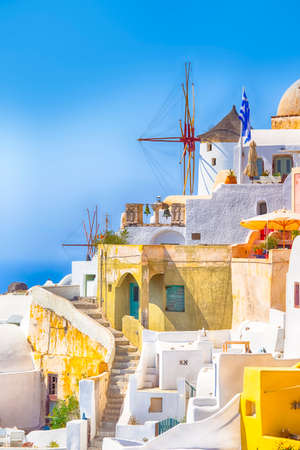 Popular Travel Destinations. Picturesque Cityscape of Oia Village in Santorini Island Located on Volcanic Calderra at Daytime. Traditional Windmills on Background. Vertical Image Composition