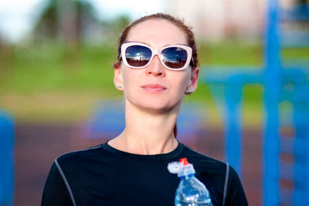 Fitness Caucasian Woman in Sportwear and Sunglasses With Water from Bottle Outdoors.Horizontal Image