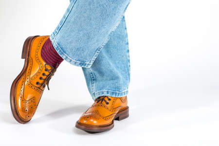 Closeup of Crossed Mens Legs in Brown Oxford Brogue Shoes. Posing in Blue Jeans Against White Background. Horizontal Image
