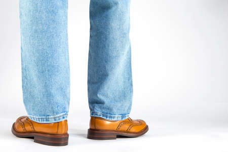 Back View of Mens Legs in Brown Oxford Brogue Shoes. Posing in Blue Jeans Against White Background. Horizontal Shot