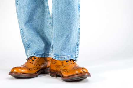 Footwear Concept. Closeup Front View of Mens Legs in Brown Oxford Brogue Shoes. Posing in Blue Jeans Against White. Horizontal Shot