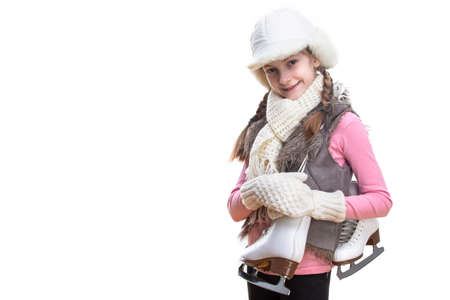 Adorable and Smiling Caucasian Blond Girl in Winter Clothes. Posing Half-Turned with Ice Skates Over Shoulder In Hands In Front. Against White.Horizontal image